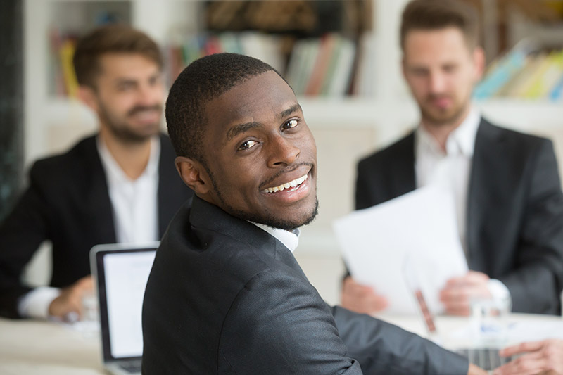 african american young male professional facing camera sitting at desk with other young professional men