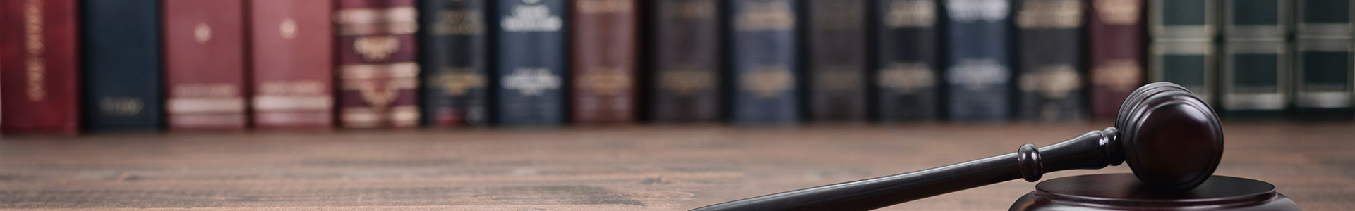 legal books on a shelf with judges gavel in front of them